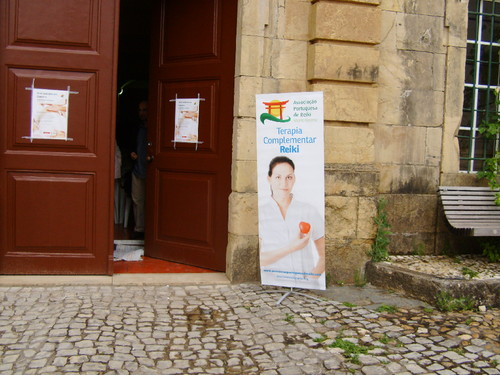 """A Associação Portuguesa de Reiki (APR) esteve em Coimbra, no passado dia 8 de junho, para uma palestra de esclarecimento sobre Reiki. O encontro decorreu em grande harmonia e contou com diversos testemunhos de médicos e doentes para quem o Reiki faz todo o sentido.  O Círculo de Cultura Portuguesa encheu-se para acolher o Reiki Solidário em Coimbra, evento da ARP integrado no Projeto 2013 – Ano da Proximidade e Solidariedade. Cerca de 100 pessoas participaram no encontro organizado pela APR, contando com o apoio de Ana Gonçalves, coordenadora do Núcleo de Coimbra.  O enfermeiro Bruno Azevedo, que integra os Órgãos Sociais da APR, falou sobre o Reiki e o âmbito da sua aplicação. O orador deu também conta da atuação da APR ao nível do esclarecimento sobre Reiki, voluntariado e criação de normas éticas e deontológicas para a prática desta terapia complementar.  Vários médicos e pacientes contribuíram com o seu testemunho sobre o recurso ao Reiki para o tratamento de situações clínicas. Nas palavras de Teresa Mendes, membro dos Órgãos Sociais da APR e uma das responsáveis pela organização do encontro, esta partilha constituiu """"uma grande mais-valia para o evento"""".  Várias pessoas presentes na assistência pediram esclarecimentos, nomeadamente uma professora que quis saber de que forma o Reiki pode ajudar numa sala de aula. Esta questão foi respondida por um professor praticante de Reiki, que revelou a forma como utiliza a filosofia do Reiki no seu dia a dia. Outras dúvidas suscitadas prenderam-se com situações de saúde no sentido de se perceber as vantagens da utilização do Reiki.  Após a palestra foram realizadas 15 sessões de Reiki a quem quis experimentar. Além de Bruno Azevedo, Teresa Mendes e Ana Gonçalves, contribuíram para a realização destas sessões Pedro Favinha (que também integra os Órgãos Sociais da APR) e Paula Robalo (voluntária da APR), entre outros."""