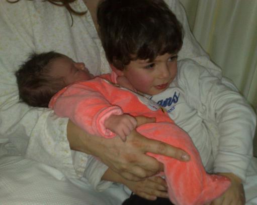 O Afonso, a aferir o peso da pequena e recém-chegada irmã...